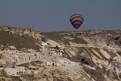 Cappadocia, Nevsehir, Turkey-May 17, 2014: Panoramic view from Goreme, traditional houses and hot air balloon. Fairy chimneys are a structure formed by rain, wind and flood waters eroding the structures made of tuffs.