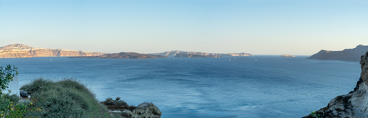 Beautiful panoramic view from Oia to caldera and volcano at golden hour. Picturesque natural background with copy space for text. Santorini island, Cyclades, Greece, Europe.