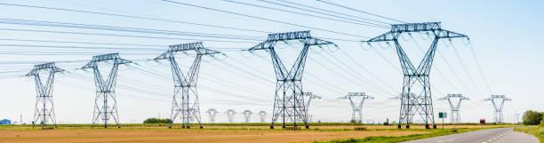 Vue panoramique d'une rangée de pylônes électriques dans la campagne. - Photo
