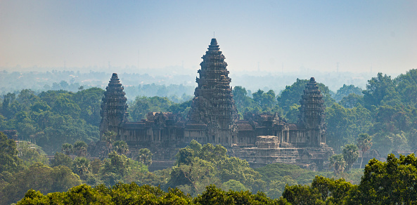 Siem Reap, Cambodia - January 24, 2020: The Angkor Wat is a Hindu temple complex in Cambodia and is the largest religious monument in the world. This photograph was taken from the hill that houses the Phnom Bakheng temple.