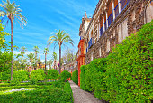 Panoramic view of big and beautiful garden - Gardens of Royal Alcazar in Seville. Spain.