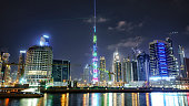 Dubai,United Arab Emirates - January 07,2018:  Downtown summer night skyline.    Panoramic view of business bay and downtown area of Dubai reflection in a river.
