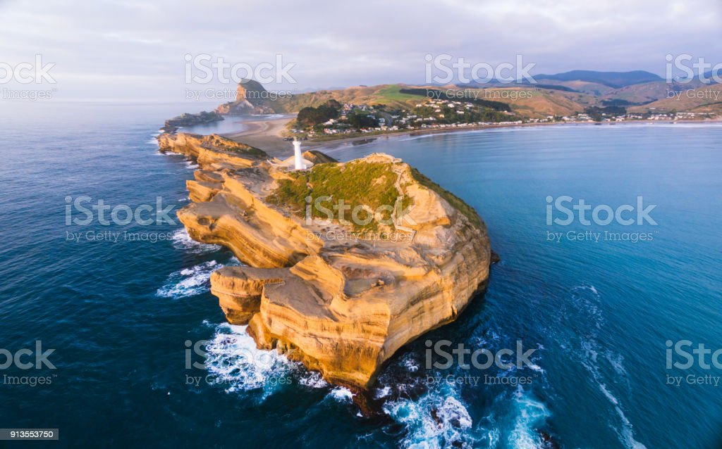 Panoramic view of Castlepoint Lighthouse with Castlepoint village in background during sunrise. stock photo
