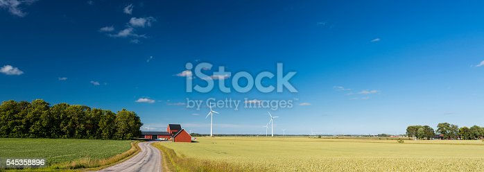In the province of Dasland in Sweden, a few wind turbines surround a traditional red Swedish farmhouse in a yellow wheat fields. The panoramic view is composed of colorful colors, the yellow wheat, a clear blue and a red farmhouse.With the wind turbines, the image also displays the high technology used for the environmental protection of the nature and the traditional farming.