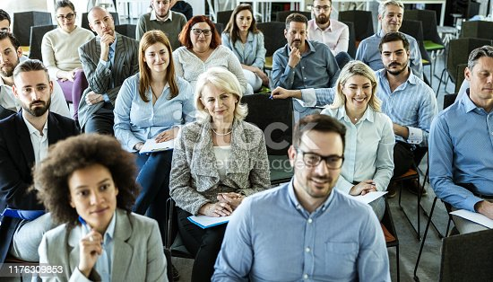 istock Panoramic view of crowd of entrepreneurs attending a business seminar in board room. 1176309853