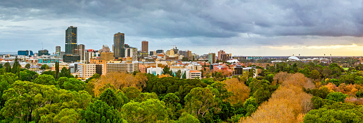 Unusual panoramic view of downtown City of Adelaide on a stormy day with the Botanic Gardens and autumn colours in the foreground, and Adelaide Oval in the right of frame.