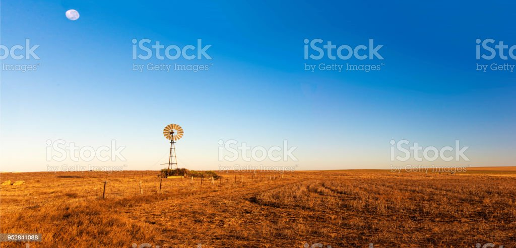 Panoramic view of early morning landscape with a windmill. stock photo