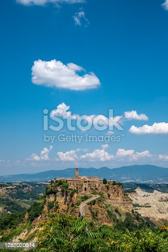 Beautiful panoramic view of famous Civita di Bagnoregio with Tiber river valley at evening, Lazio, Italy - Vertical shot