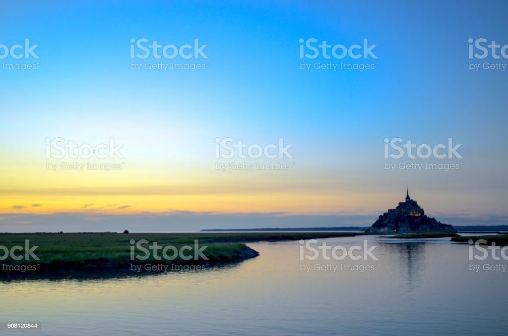 Panoramic view of famous Le Mont Saint-Michel tidal island in beautiful twilight during blue hour at dusk, Normandy, northern France stock photo