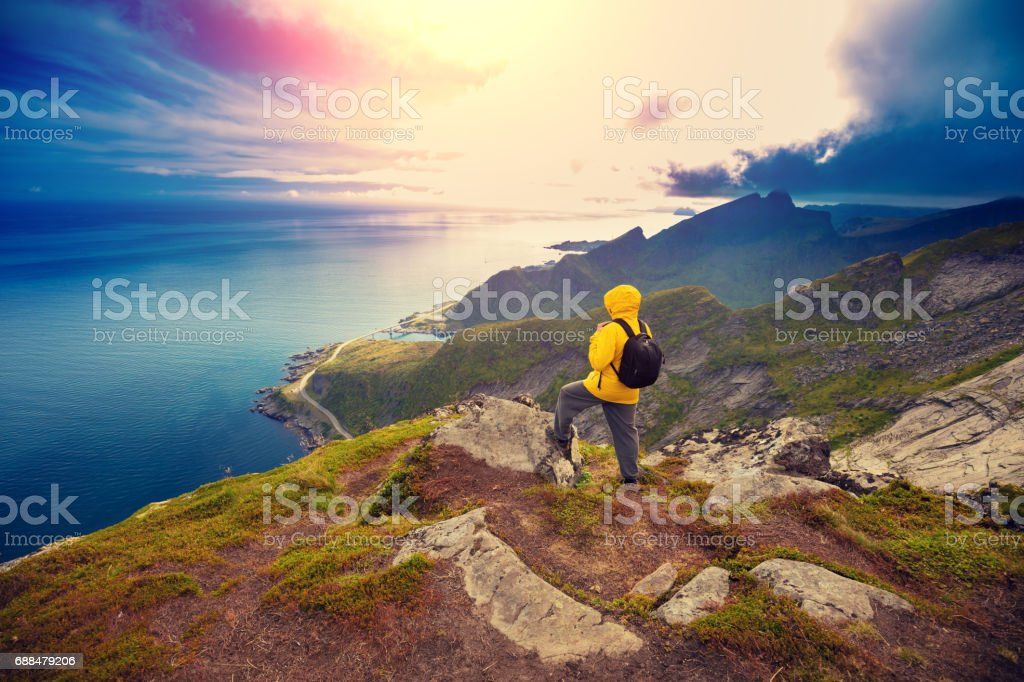 Panoramic view of fjord and fishing village. Man tourist standing on a cliff of rock. Beautiful mountain landscape. Nature Norway, Lofoten islands stock photo