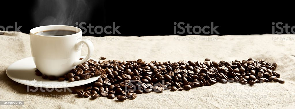 Panoramic view of frothy coffee cup, beans on fabric flax stock photo