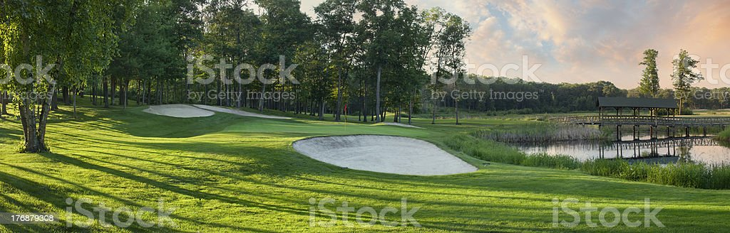 Panoramic view of golf green with white sand traps stock photo