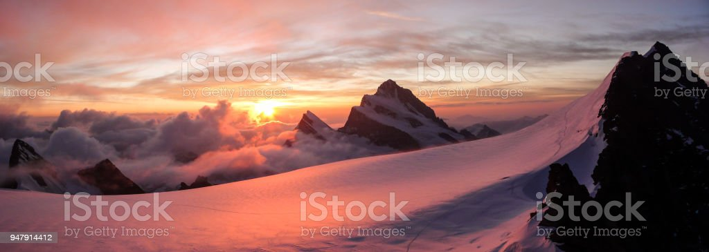 panoramic view of gorgeous pink sunrise over glacier and high mountain peaks in the Alps stock photo