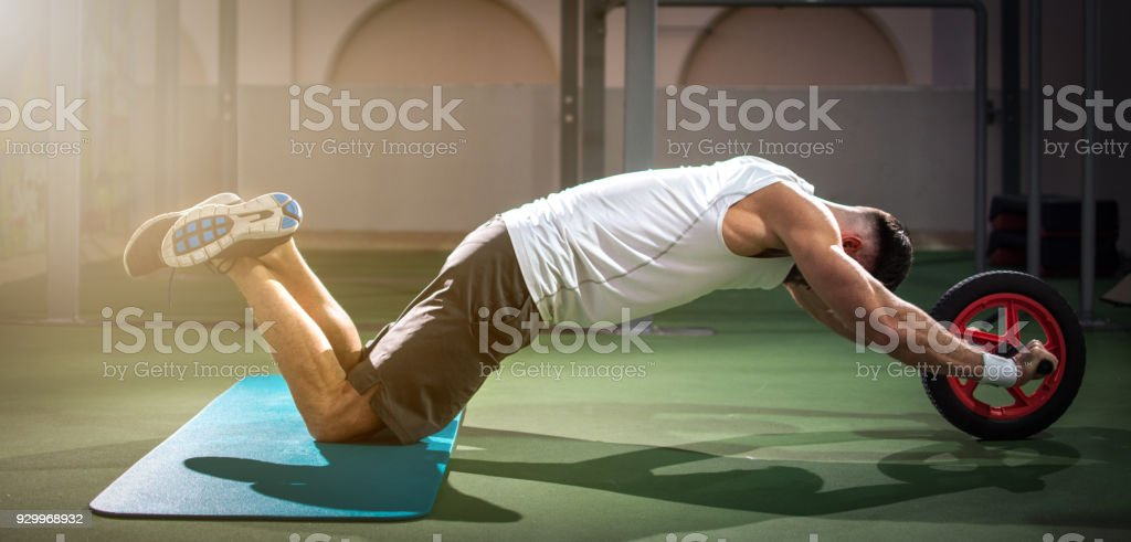 Panoramic view of handsome man working out with fitness wheel at rooftop, outdoor gym. stock photo