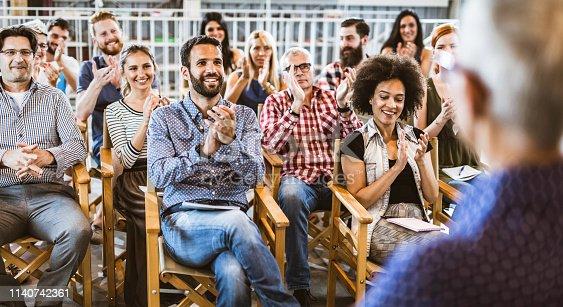 894290604 istock photo Panoramic view of happy entrepreneurs applauding on training class. 1140742361