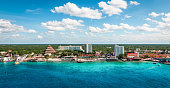 Panoramic view of popular cruise and tourist destination with buildings along the coastline at the port of Cozumel in Mexico. Blue sky and clouds. Beautiful summer day. Caribbean Sea with turquoise colored water.