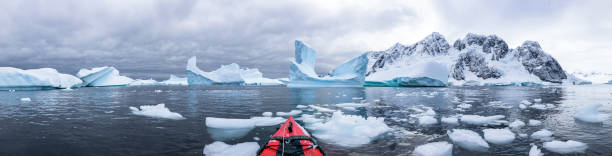 Panoramic view of kayaking in the Iceberg Graveyard in Antarctica stock photo