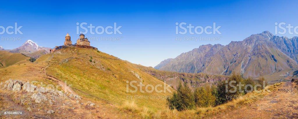 Panoramic view of Kazbegi mountain range and Tsminda Sameba church, Georgia stock photo