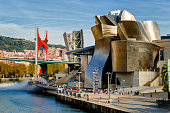 Bilbao, Spain - September 24, 2017: Panoramic view of La Salve Bridge and Guggenheim Museum, designed by Frank Gehry, on the bank of Nervion river. A famous and very popular place for worldwide tourism which has boosted Bilbao's economy with its astounding success. The Guggenheim Museum is a fusion of swirling forms that responds to an intricate program and an industrial and urban context.