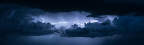 panoramic view of lightning between the clouds - storm stock photos and pictures