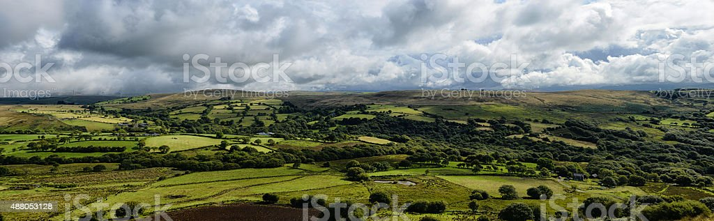 Panoramic view of lush countryside with cloudy sky stock photo