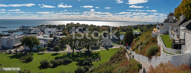 A panoramic view of Mackinac Island.  Shot from above the city, Fort Mackinac is on the right of the frame and the Mackinac Bridge can be seen in the background.  Mackinac Island is a popular tourist attraction.