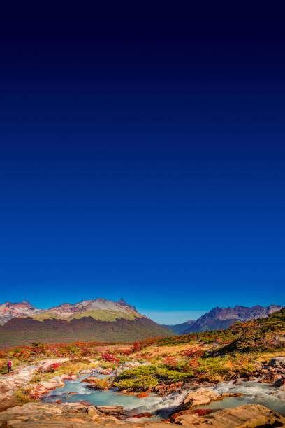 Panoramablick auf den magischen bunten Märchenwald im Nationalpark Tierra del Fuego mit einem einsamen Wanderer, Patagonien, Argentinien, Herbstzeit, blauer Himmel – Foto