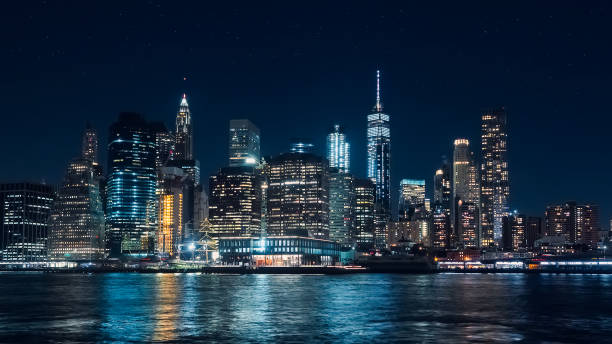 Panoramic view of Manhattan skyscrapers at night, at Christmas, from the Dumbo area in Brooklyn Panoramic view of Manhattan skyscrapers at night, at Christmas, from the Dumbo area in Brooklyn new york state stock pictures, royalty-free photos & images
