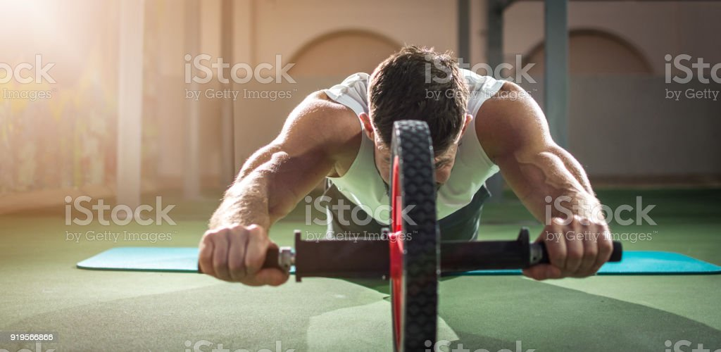 Panoramic view of muscular man exercising with abdominal roller in gym. stock photo
