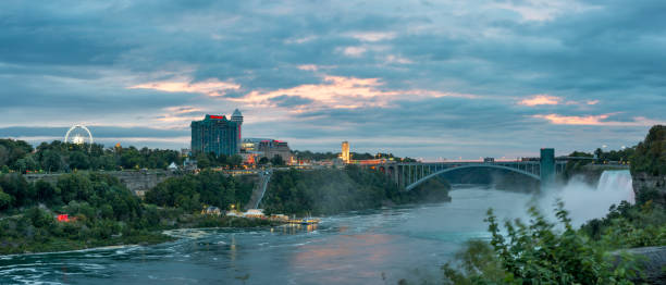 Panoramic view of Niagara falls and the Rainbow Bridge after sunset Niagara Falls, NY, United States - Sep 24, 2018: The Canada side small town of the same name and the Rainbow Bridge between the two countries after sunset, seen from the Niagara Falls State Park. rainbow bridge ontario stock pictures, royalty-free photos & images