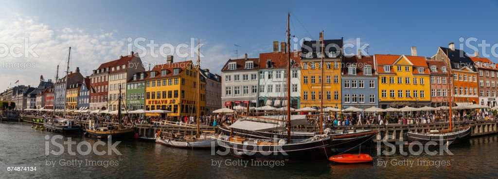 COPENHAGEN, DENMARK - 25 JUN 2016: Panoramic view of Nyhavn canal is full of people at sunny day stock photo
