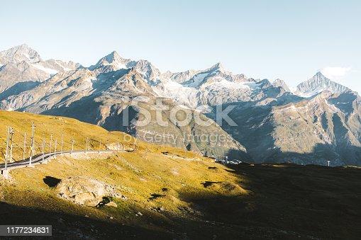 Sunny sunrise above mountains and railway in Gornegrat area, Zermatt, Valais canton, Switzerland