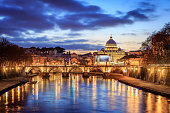 St. Peter's cathedral over bridge and Tiber river in Rome at sunset, Italy at fall day