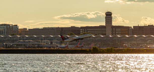 Panoramic view of Ronald Reagan National Airport across Potomac River at sunset. i Washington DC, USA 10/03/2020: Panoramic view of Ronald Reagan National Airport across Potomac River at sunset. image features the tower, terminals, parked planes and a Delta Airline plane taking off. ronald reagan washington national airport stock pictures, royalty-free photos & images