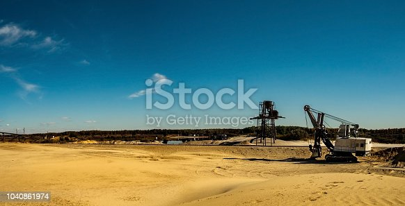 Panoramic view of sand quarry, mining of yellow construction sand, pumping sand from a nearby pond with help of powerful pumps, post-apocalyptic landscape with abandoned machine, Chelyabinsk, Russia