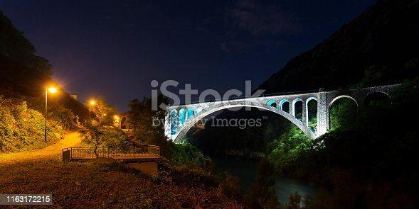 Illuminated the most beautiful old stone build Solkan Bridge near Nova Gorica (Slovenia - Europe) with the biggest arch - architectural feature with night sky above and the river under.