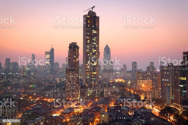 Panoramic view of south central Mumbai - the financial capital of India - at golden hour showing vast contrast in the living conditions of people with dwellings of lower middle class in foreground and towers where elite stay in the far background.