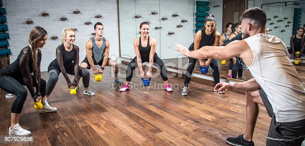 istock Panoramic view of sporty people training with weights with assistance of their coach at health club. 927929836