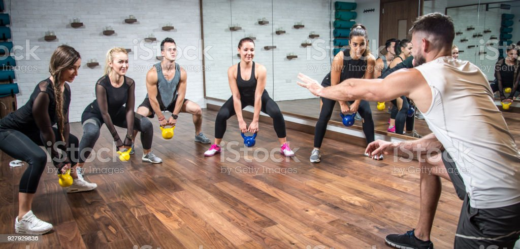 Panoramic view of sporty people training with weights with assistance of their coach at health club. stock photo