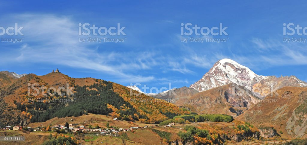 Panoramic view of Stepantsminda village and Trinity church, Georgia stock photo