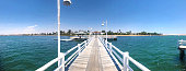 Paracas, Peru - March 4 2018: Panoramic view of symmetrical pier at national natural reserve of Paracas in Ica, Peru. White wooden bridge in bay.