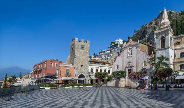 陶爾米納主廣場 (廣場九愚人節) 與聖朱塞佩 · 教堂、 鐘塔和山埃特納火山上背景-陶爾米納,西西里島,義大利的全景視圖 - 陶爾米納 個照片及圖片檔
