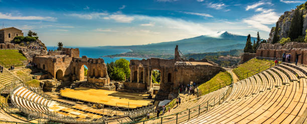 Panoramic view of the Ancient Theatre in Taormina, Sicily The Greek Theater in Taormina is a spectacular architectural sight. Its position is unique as it overlooks the beautiful Mediterranean sea and magnificent Mount Etna sicily stock pictures, royalty-free photos & images