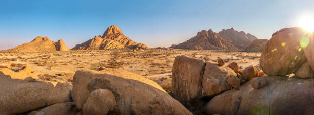 Panoramic view of the barren rocky landscape of Spitzkoppe, Damaraland in Namibia, with its huge granite boulders and mountains, and sparse vegetation. stock photo
