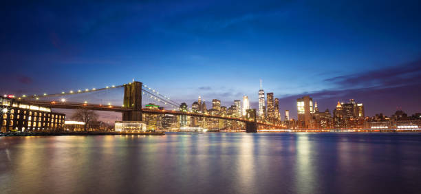 Panoramic view of the Brooklyn Bridge and Manhattan Skyline The lights of the Brooklyn Bridge and Manhattan skyscrapers reflected in the water of the East River at dusk. letterbox format stock pictures, royalty-free photos & images