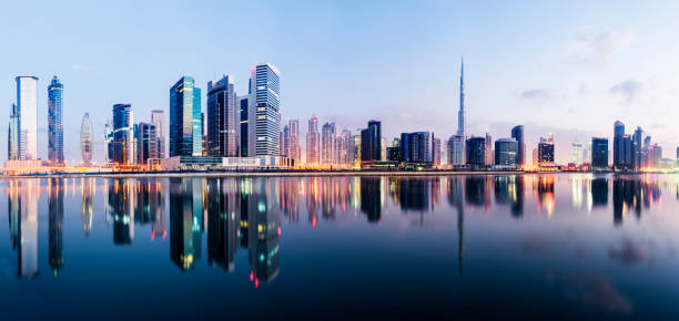 Panoramic view of the Dubai downtown and business park district at twilight with reflection in the still lake water, United Arab Emirates stock photo