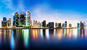 Panoramic view of the Dubai downtown and business park district skyline at twilight with reflection in the still lake water, United Arab Emirates