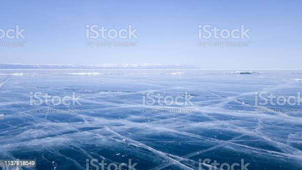 Photo of Panoramic view of the endless ice of lake Baikal in winter. Deep cracks on the surface of bright blue ice. Sunny clear weather in frosty Siberia