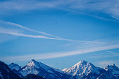 Panoramic view of the European Alps, many colorful hot air balloons in the sky