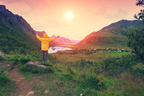 Vista panorâmica do fiorde. Tempo de Crepúsculo com um incrível céu laranja. O jovem com mãos de pé o ar um penhasco de pedra e olhando por do sol. Bela paisagem montanhosa ao pôr do sol. - foto de acervo